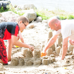 A boy and a man build a sandcastle on the beach at Miller Family Camp