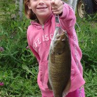 A proud girl shows off her prize catch of a fish caught from Miller Lake
