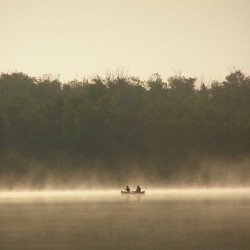 A canoe in the early morning mist of Miller Lake