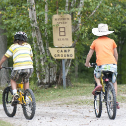 Two kids ride bikes past a sign at Miller Family Camp.