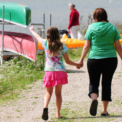 A girl and woman walk past canoes on the shoreline at Miller's Family Camp.