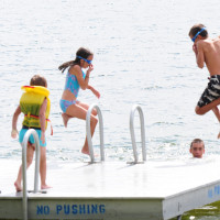 Children jump into the warm water of Miller Lake, Ontario.