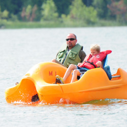 A father and son enjoy a leisurely expedition in a paddleboat.